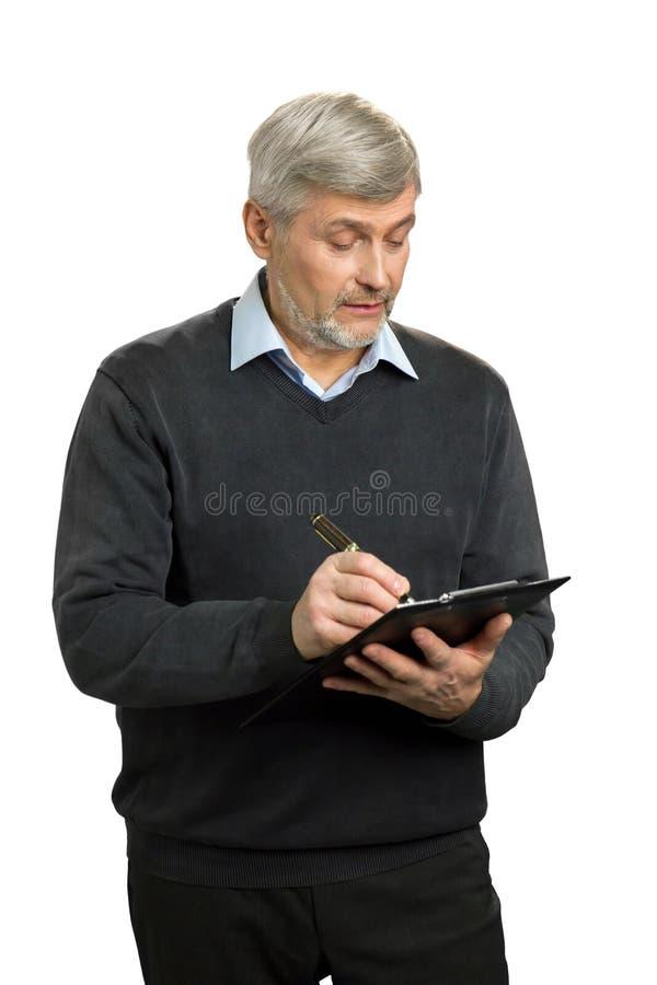 Überzeugtes älteres Aufsichtskraftschreiben auf Klemmbrett stockfotos
