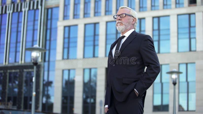 Überzeugtes älteres Geschäftsmannstellungs-Außenseitenbürogebäude, männlicher Direktor stockfotografie