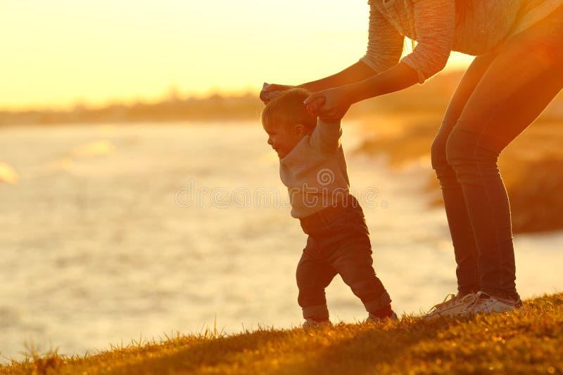 Überzeugtes Baby, das lernen zu gehen und Mutter, die ihm hilft stockfotos
