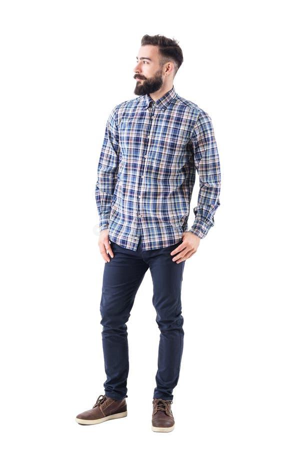Überzeugtes entspanntes bärtiges hübsches Mode-Modell im karierten Hemd mit den Daumen in den Taschen, die weg schauen stockfotos