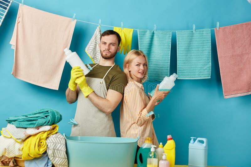 Überzeugtes fleißiges Paar wird alle schmutzige Kleidung loswerden lizenzfreies stockfoto