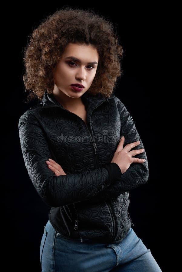 Überzeugtes gelocktes Mädchen, das schwarze Jacke und Blue Jeans trägt stockfoto