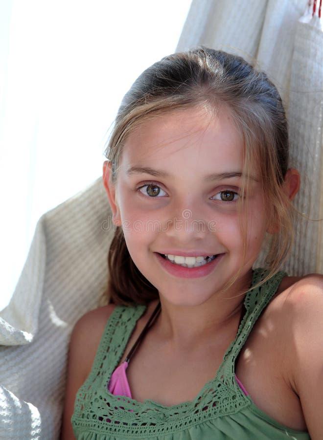 Überzeugtes junges Mädchen, das in der Hängematte auf Ferien sitzt stockfotos