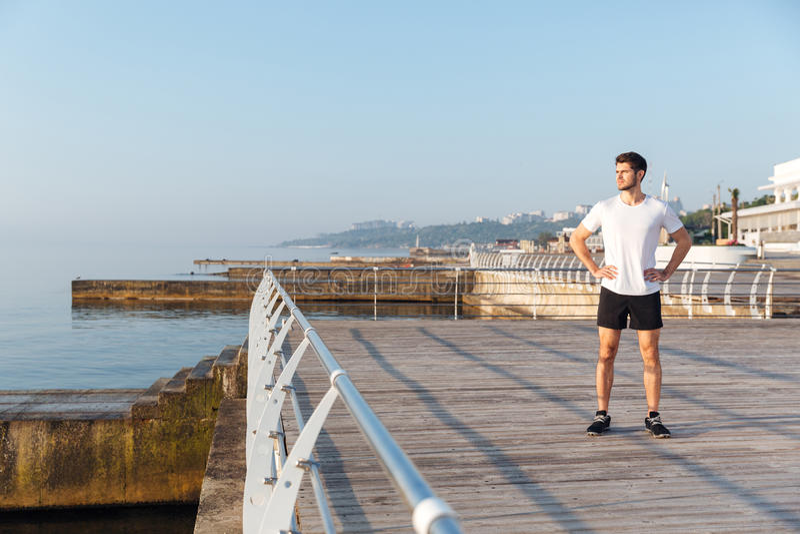 Überzeugtes junges spotrsman, das auf Pier steht lizenzfreies stockfoto