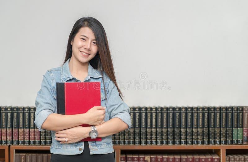 Überzeugtes lächelndes asiatisches Mädchen des Studenten in der Bibliotheksuniversität lizenzfreie stockbilder