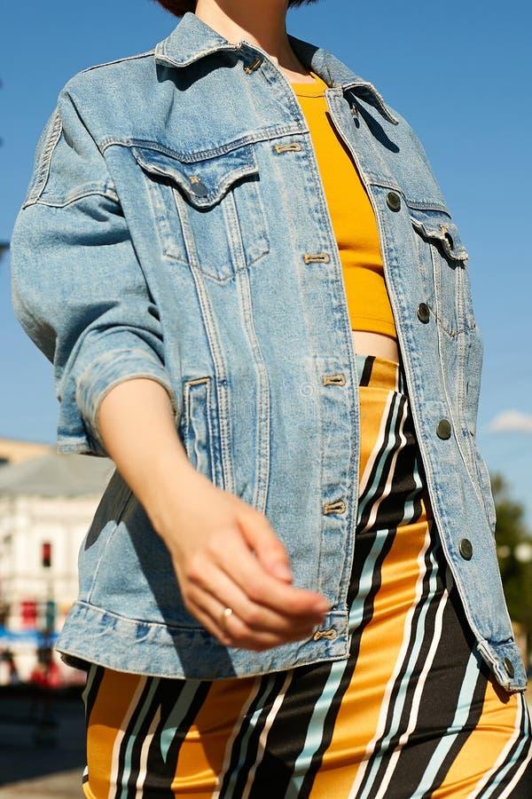 Überzeugtes Mädchen in der modernen Kleidung des Sommers geht und bewegt ihre Hände wellenartig stockfotos