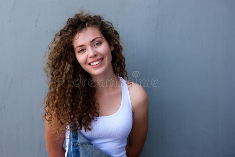 Überzeugtes Mädchen des jungen jugendlich, das im Overall lächelt lizenzfreies stockbild
