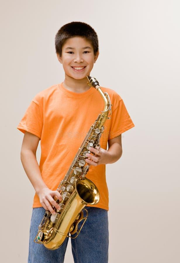 Überzeugtes Musikerholding-Saxophon stockfoto