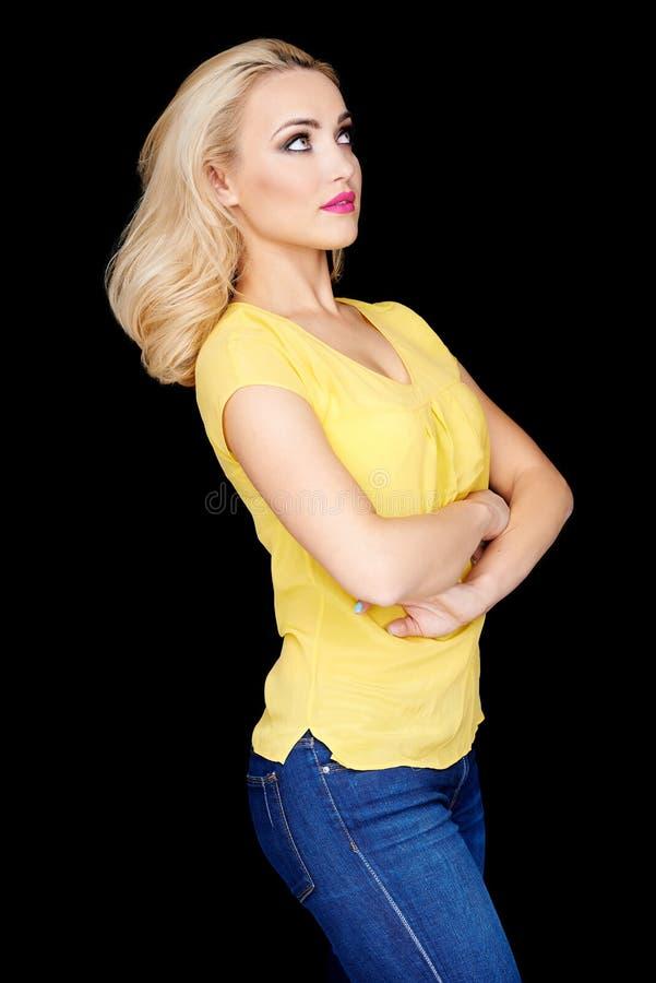 Überzeugtes schönes blondes mit den gefalteten Armen stockbild