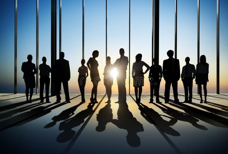 Überzeugtes Schattenbild von den Geschäftsleuten, die herein für die Kamera aufwerfen stockbild