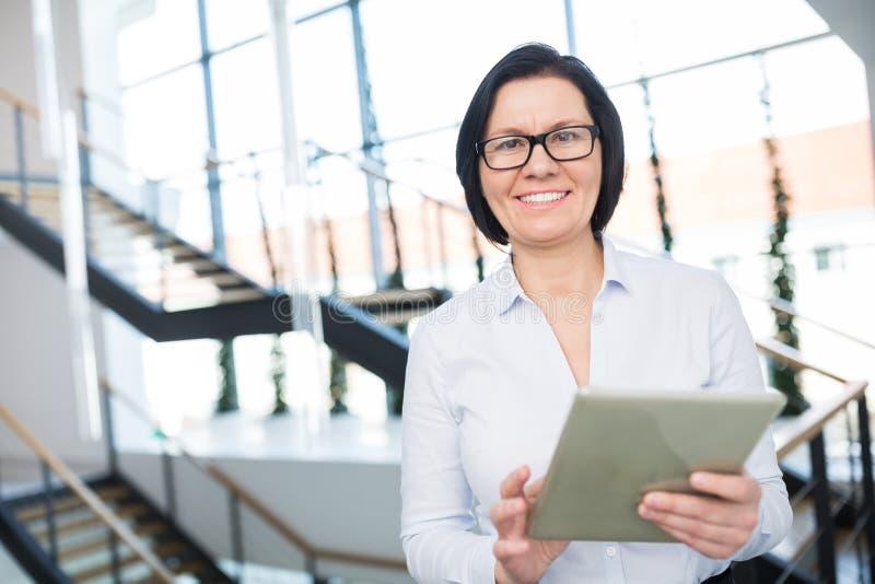 Überzeugtes Tablet Geschäftsfrau-Smiling While Usings Digital lizenzfreie stockfotografie