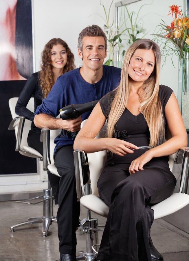 Überzeugtes Team Of Hairstylists At Beauty-Wohnzimmer lizenzfreie stockbilder