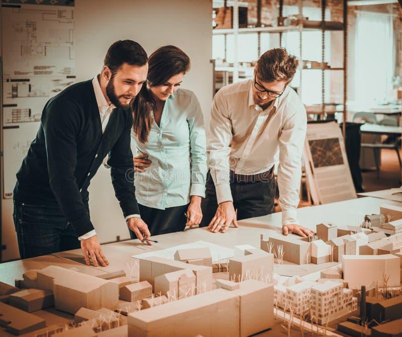 Überzeugtes Team von den Ingenieuren, die in einem Architektenstudio zusammenarbeiten stockbilder