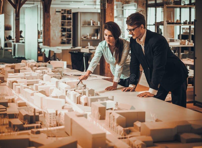 Überzeugtes Team von den Ingenieuren, die in einem Architektenstudio zusammenarbeiten lizenzfreies stockbild