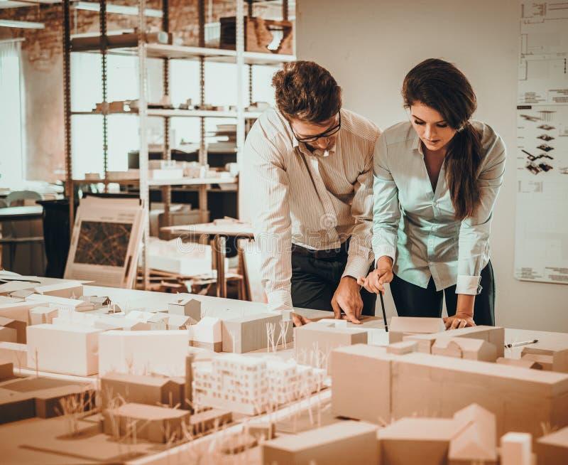 Überzeugtes Team von den Ingenieuren, die in einem Architektenstudio zusammenarbeiten stockfotografie