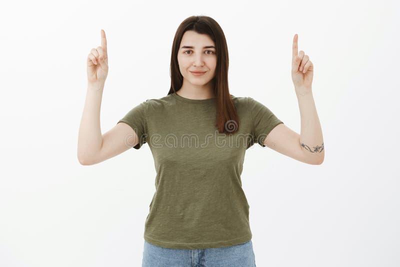 Überzeugtes und ehrgeiziges schönes optmistic Mädchen mit dem braunen Haar- und Tätowierungslächeln selbstsicher und anspruchsvol stockbild