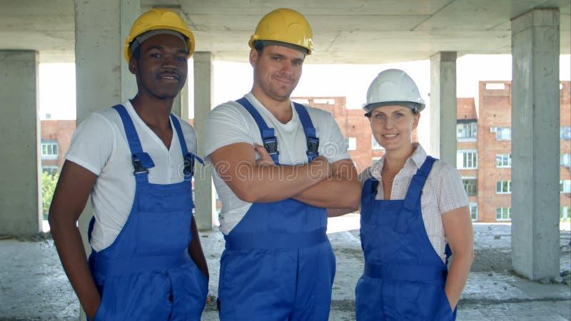 Überzeugtes verschiedenes Team von den Arbeitern und von Frauen, die in ihren Jeansstoffen und in Hardhats lächelnd an der Kamera stockfotografie