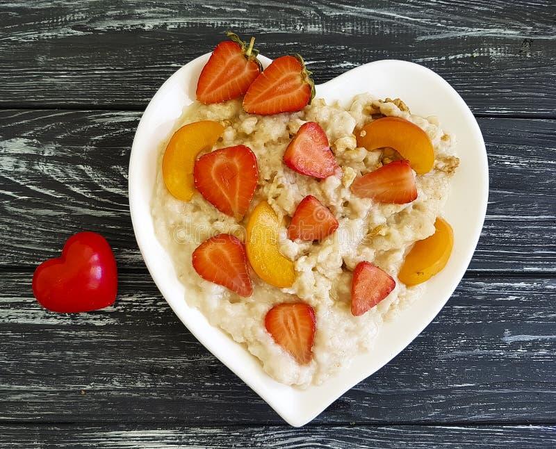 Überziehen Sie Herzhafermehlbrei, Erdbeere, Aprikose auf einem hölzernen Hintergrund stockfotografie