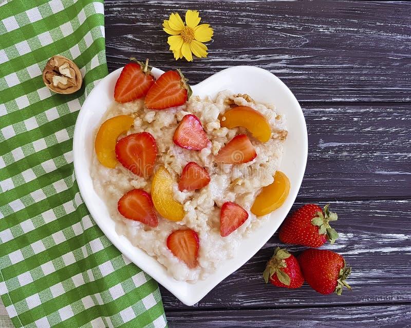 Überziehen Sie Herzhafermehlbrei, frische Sommererdbeere, Aprikose auf einem hölzernen Hintergrund stockfotos