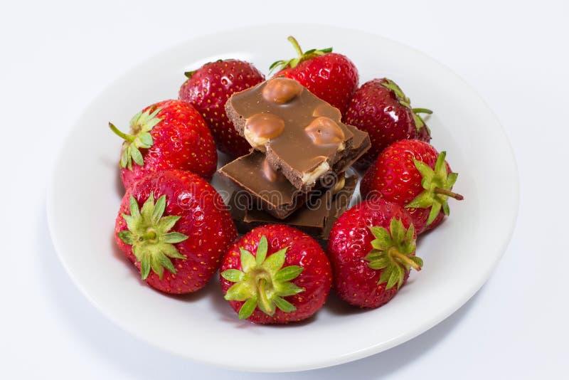 Überziehen Sie voll von den geschmackvollen saftigen Erdbeeren und von der Schokolade, die auf schwarzem Hintergrund lokalisiert  lizenzfreie stockfotos