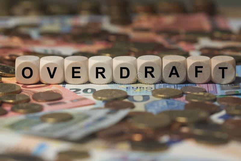 Überziehung - Würfel mit Buchstaben, Geldsektorausdrücke - Zeichen mit hölzernen Würfeln stockfoto