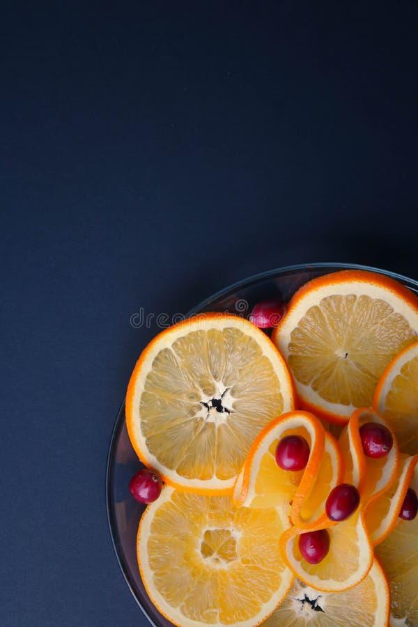 Überzogene Moosbeeren und saftige orange Scheiben stockbild