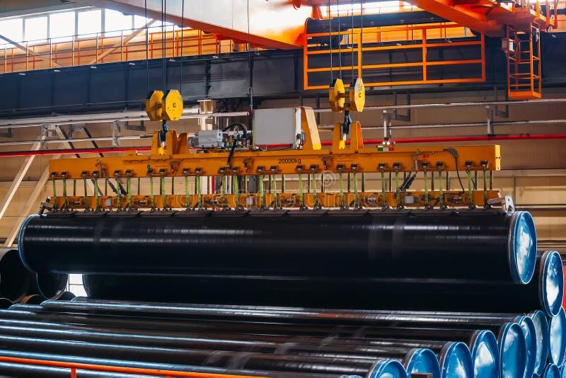 Überzogener Rohrtransport durch Laufkran mit dem Vakuum, das Greifer behandelt lizenzfreie stockfotografie