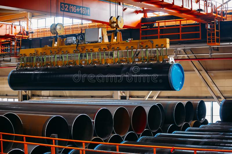 Überzogener Rohrtransport durch Laufkran mit dem Vakuum, das Greifer behandelt stockfoto