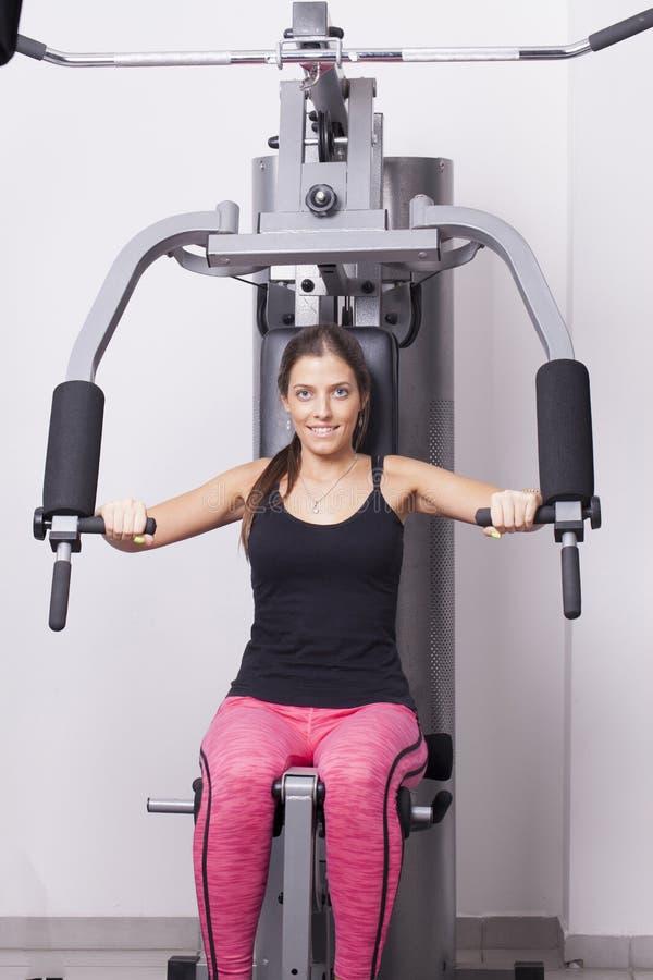 Übungen der jungen Frau in einer Turnhalle lizenzfreie stockfotografie