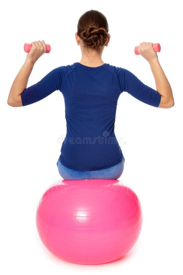 Übungen mit Dumbbells auf einer gymnastischen Kugel stockfotos