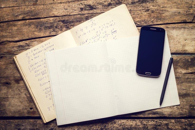 Übungsbuch mit Smartphone und Stift auf altem Holztisch stockfotografie