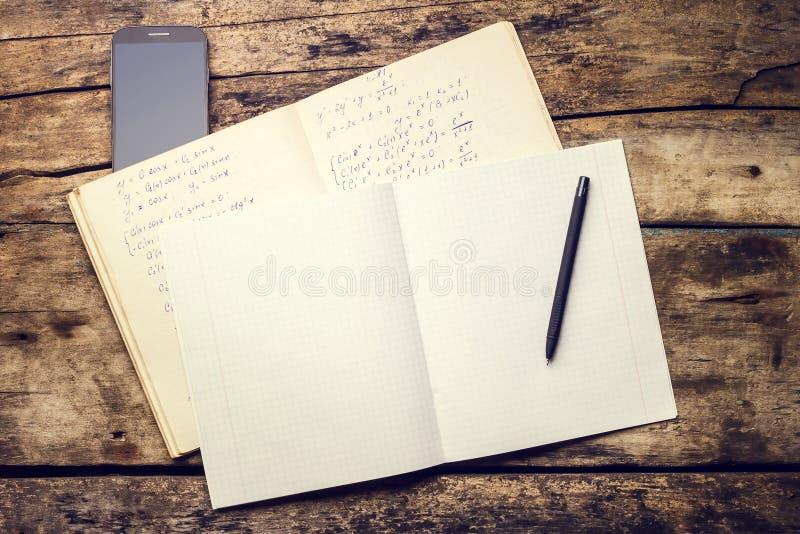 Übungsbuch mit Smartphone und Stift auf altem Holztisch stockbild