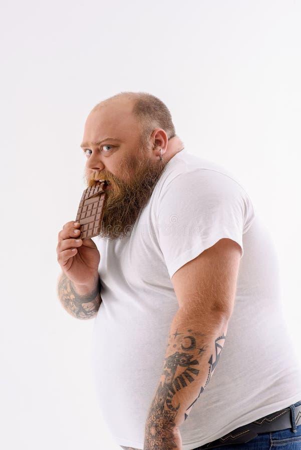 Żądnego męskiego fatso zjadliwy słodki jedzenie zdjęcia royalty free
