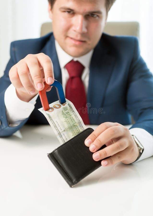 Żądny biznesmena ciągnięcia pieniądze out portfel z use magnes obraz stock
