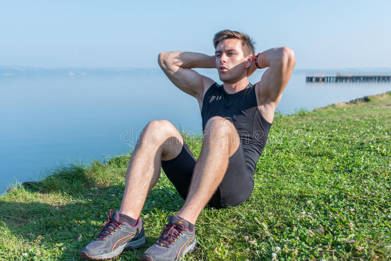 ćwiczący sprawność fizyczną jego mężczyzna odbicia szkolenia woda Młody sportowiec robi brzusznym chrupnięciom outdoors obrazy stock