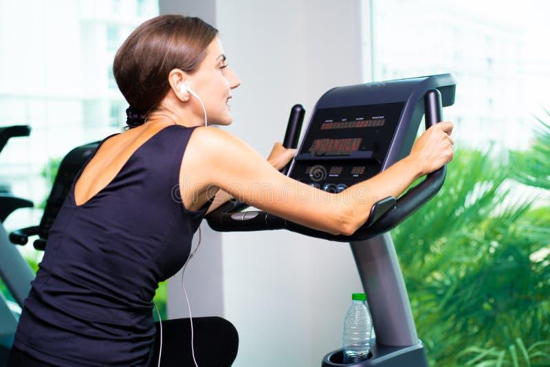 Ćwiczenie roweru cardio trening przy sprawności fizycznej gym bierze ciężar stratę kobieta kobieta słucha muzyka na hełmofonach a fotografia royalty free
