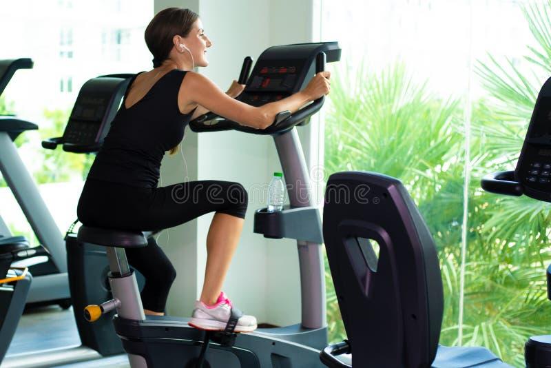 Ćwiczenie roweru cardio trening przy sprawności fizycznej gym bierze ciężar stratę kobieta kobieta słucha muzyka na hełmofonach a fotografia stock