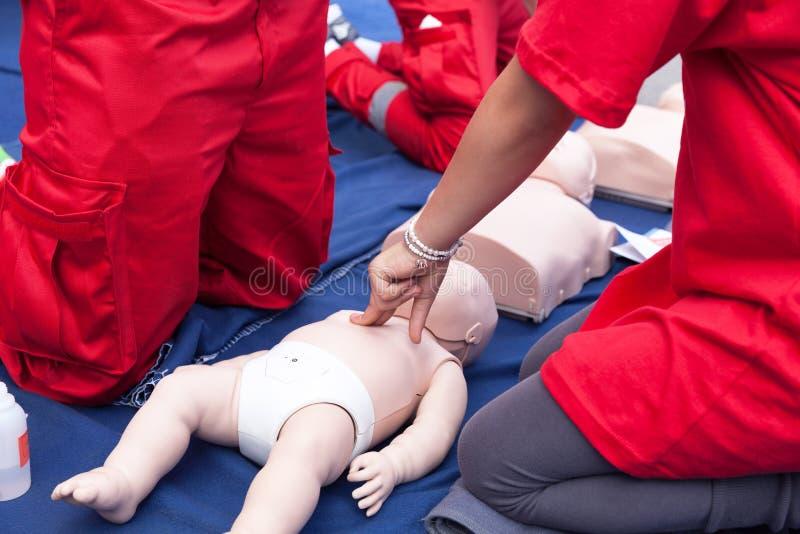 Ćwiczy CPR dziecko na dziecięcej atrapie zdjęcie royalty free