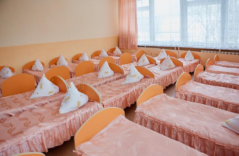 Łóżka i łóżka polowe w jaskrawy barwiącym dormitorium pepiniera Mnóstwo dzieci łóżka polowe zdjęcie stock