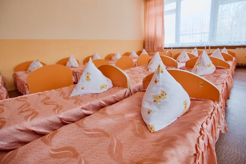 Łóżka i łóżka polowe w jaskrawy barwiącym dormitorium pepiniera Mnóstwo dzieci łóżka polowe fotografia royalty free