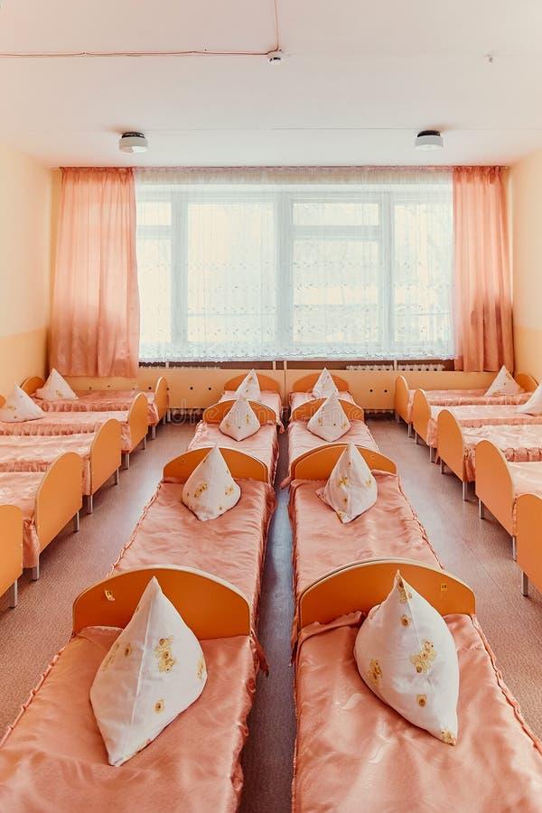 Łóżka i łóżka polowe w jaskrawy barwiącym dormitorium pepiniera Mnóstwo dzieci łóżka polowe zdjęcie royalty free