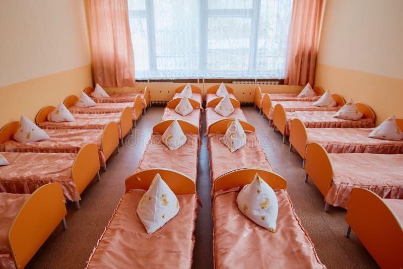 Łóżka i łóżka polowe w jaskrawy barwiącym dormitorium pepiniera Mnóstwo dzieci łóżka polowe zdjęcia royalty free