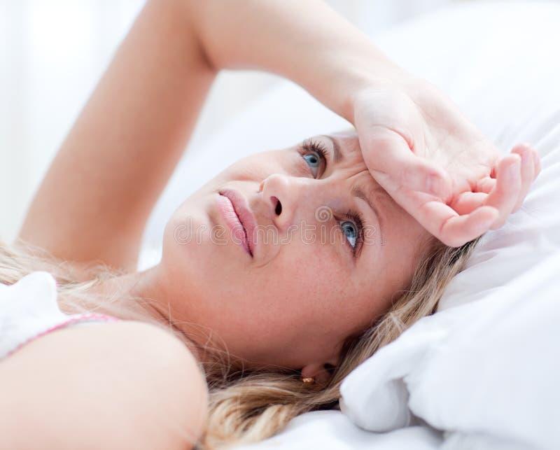 łóżko ma łgarskiej migreny spęczenia kobiety zdjęcie stock