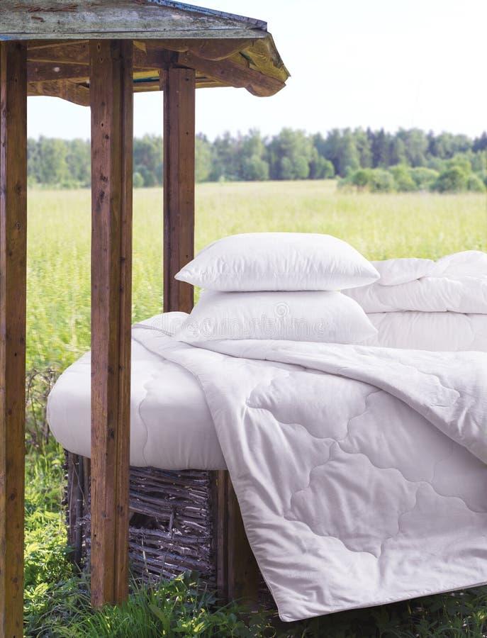 Łóżko z łóżkową pościelą w naturze Śnieżnobiały łóżko przeciw pięknemu natura widokowi zdjęcia royalty free