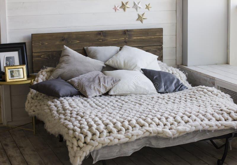 Łóżko z drewnianym headboard, poduszki, trykotowa koc scandinavia fotografia royalty free