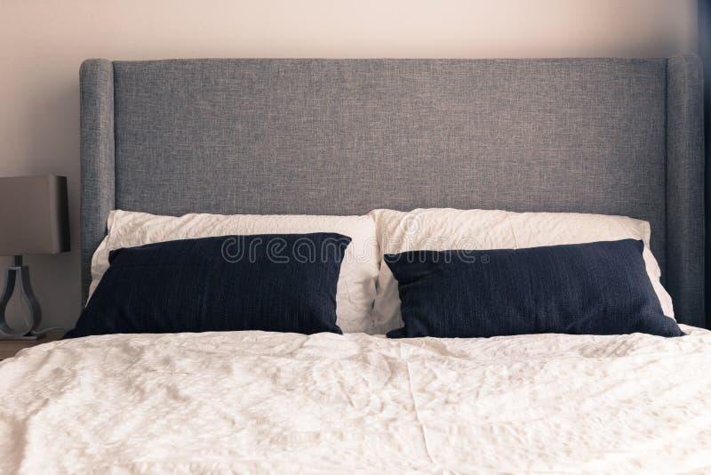 Łóżko z zmarszczenia białym duvet w wąskim kondominium obrazy stock