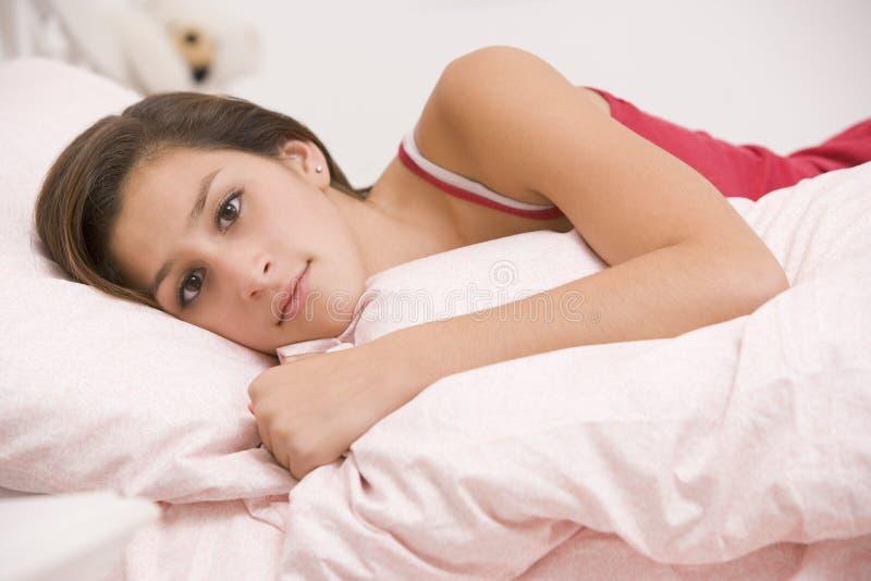 łóżkowa dziewczyna ona przyglądający łgarski chory nastoletni obraz royalty free