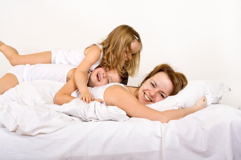łóżkowa szczęśliwa dzieciaków ranek kobieta obrazy stock