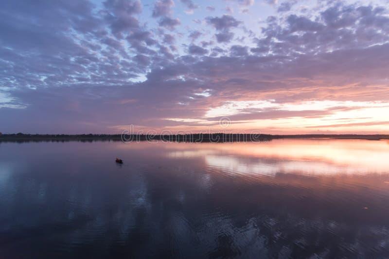 Łódź jeżdżenie w dużej rzece w zmierzchu twiligh i czasie obraz royalty free
