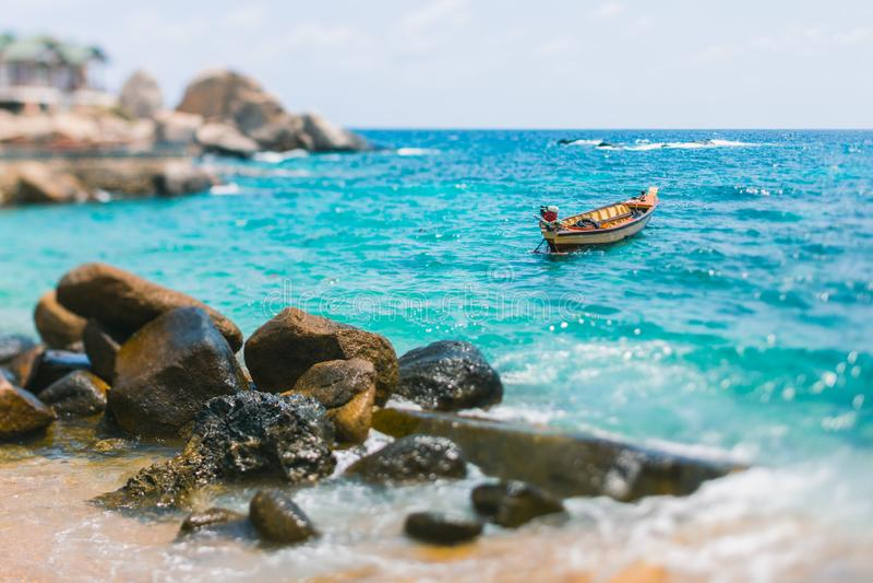 Łódź kiwa na turkusowych falach Wybrzeże Koh Tao wyspa W Tajlandia Kamienie na linii brzegowej obraz stock